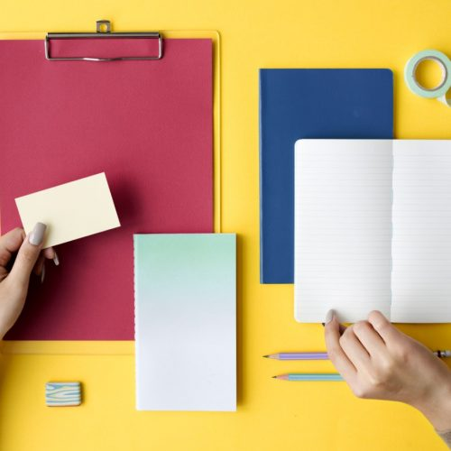 hand-open-blank-notebook-and-stationery-on-yellow-PDYN6EB
